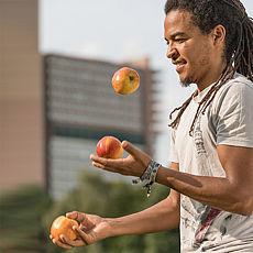 Junger Mann jongliert mit Äpfeln