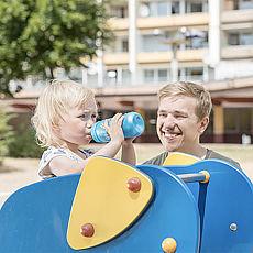 Vater mit Kind auf Spielplatz